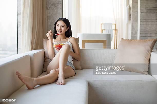 Young woman eating fruit salad on sofa
