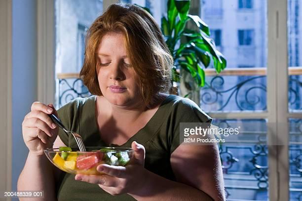 young woman eating fruit salad - blond mollig frau stock-fotos und bilder