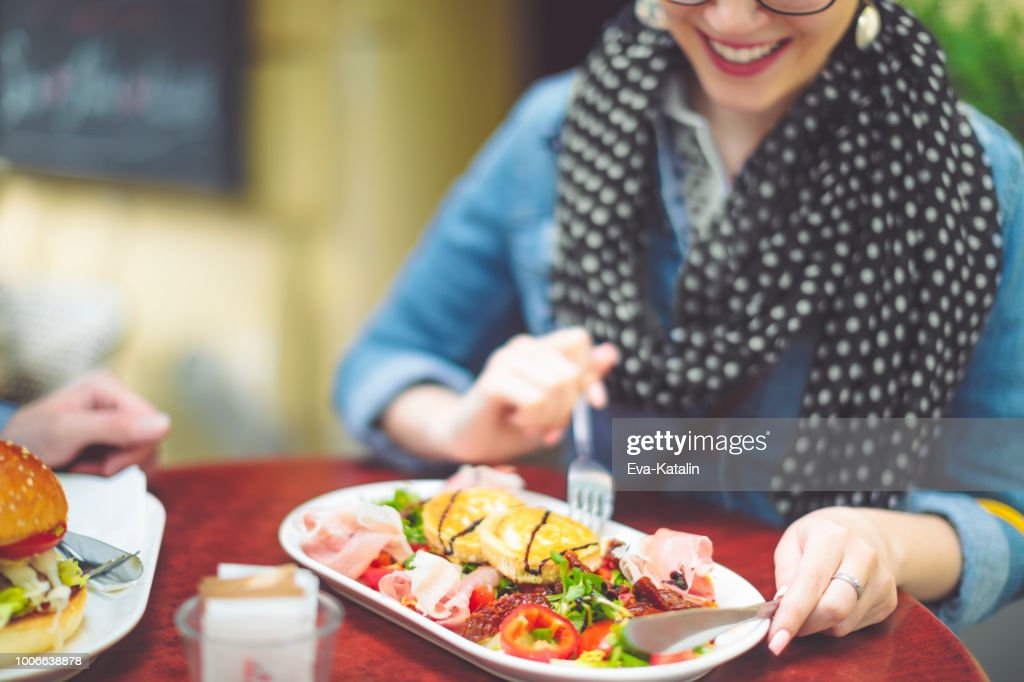 Young woman eating goat cheese salad : Stock Photo