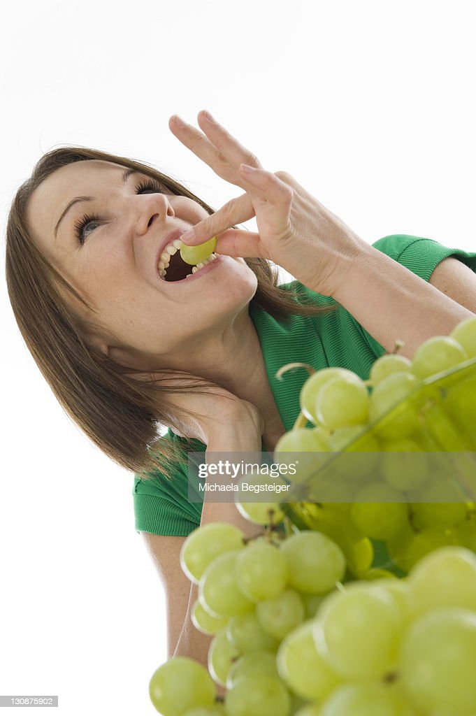 Young Woman Eating Grapes Stock Photo Getty Images