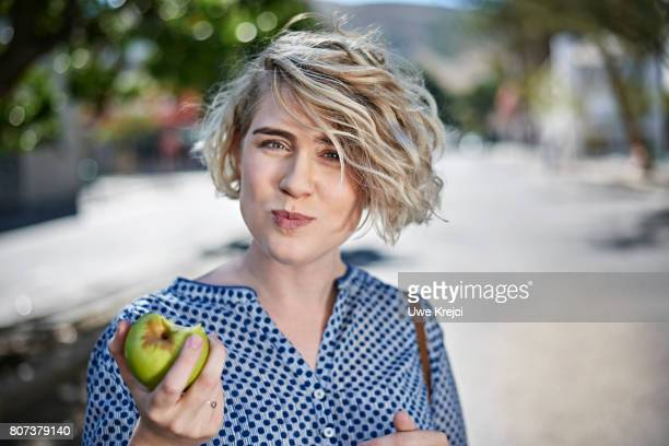 young woman eating green apple - hipster person stock-fotos und bilder