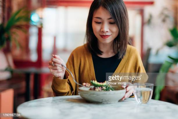 young woman eating green salad at restaurant - eating stock pictures, royalty-free photos & images