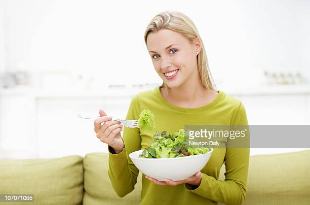 Young woman eating healthy food, smiling