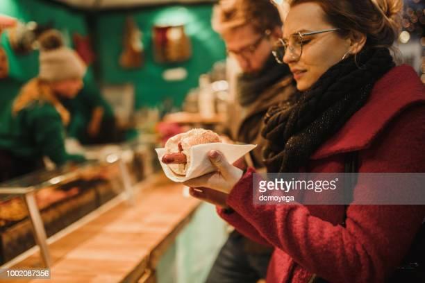 jeune femme manger des hot-dogs dans la rue - bade wurtemberg photos et images de collection
