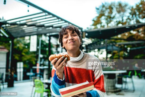 young woman eating hot dog on the street - battered woman stock pictures, royalty-free photos & images