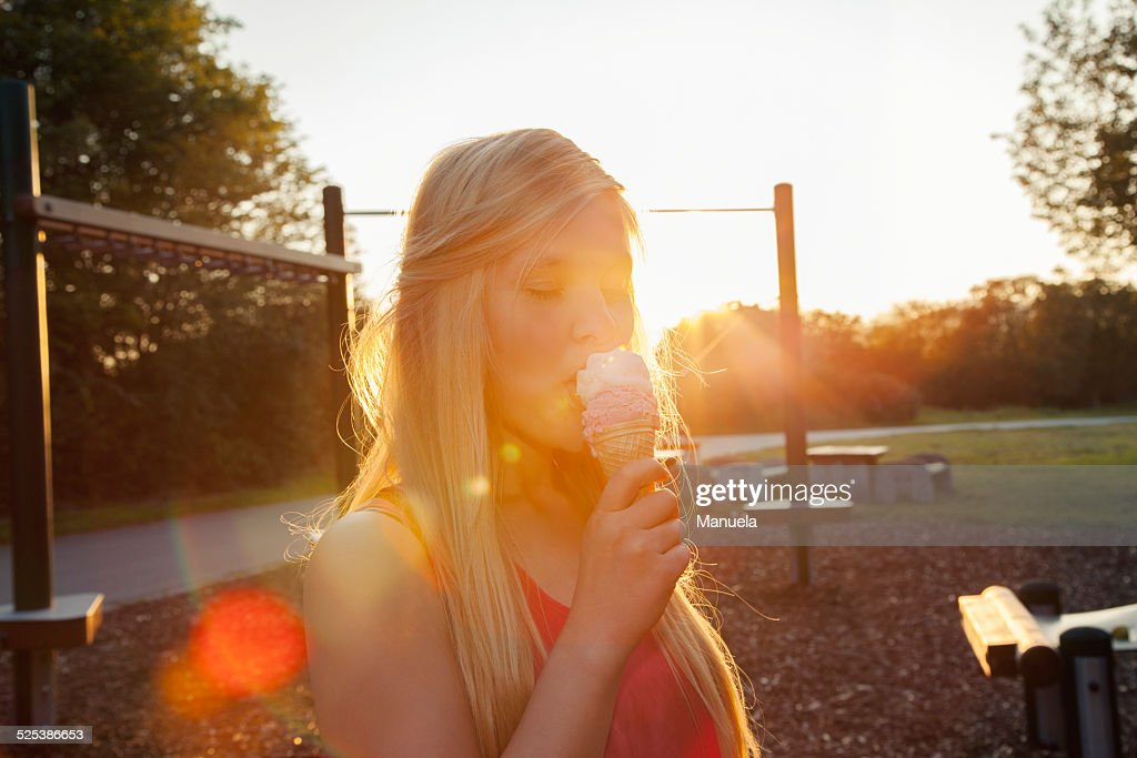 Young woman eating ice cream cone in park at sunset : Stock Photo