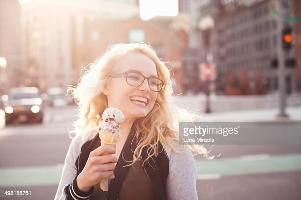 Young woman eating ice cream in street