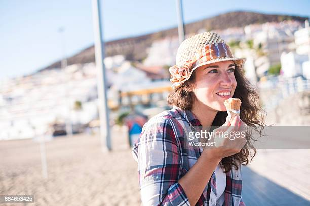 Young woman eating ice cream on the beach