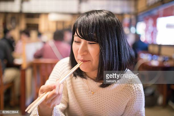 Young woman eating Japanese food with chopsticks