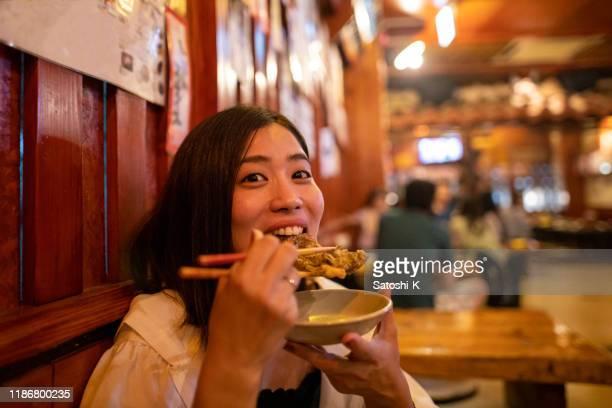 居酒屋で日本の「もずく天ぷら」を食べる若い女性 - 高級グルメ ストックフォトと画像