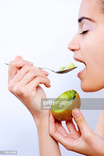 young woman eating kiwi