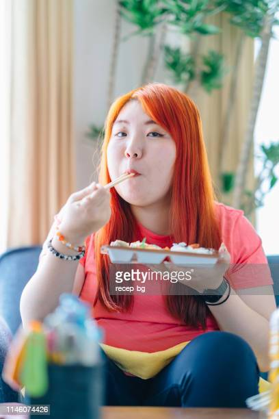 young woman eating lunch at home - chubby asian woman stock pictures, royalty-free photos & images