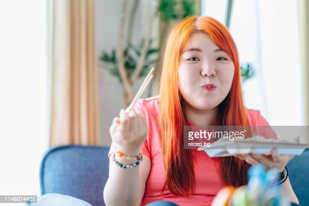 young woman eating lunch at home - fat asian woman stock pictures, royalty-free photos & images