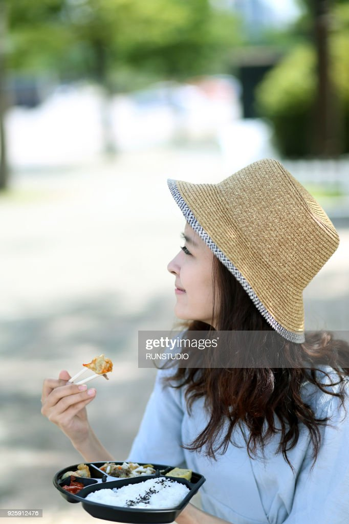 Young Woman Eating Lunch Box Outdoors
