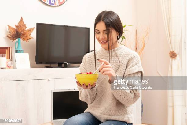 young woman eating muesli breakfast - tempio pausania stock pictures, royalty-free photos & images