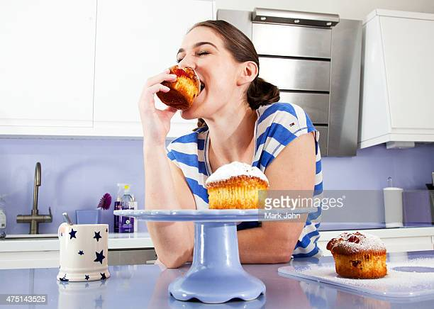 Young woman eating muffin
