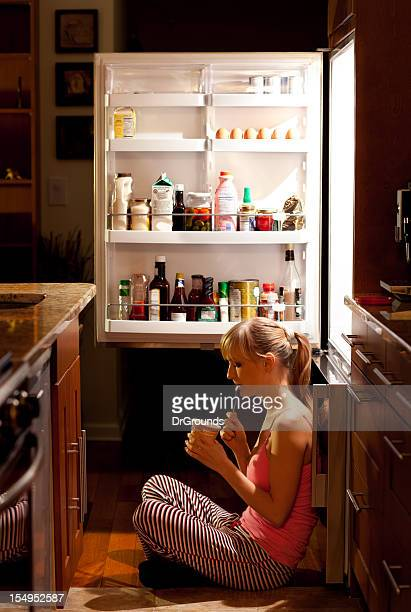 Young woman eating near refrigerator at night