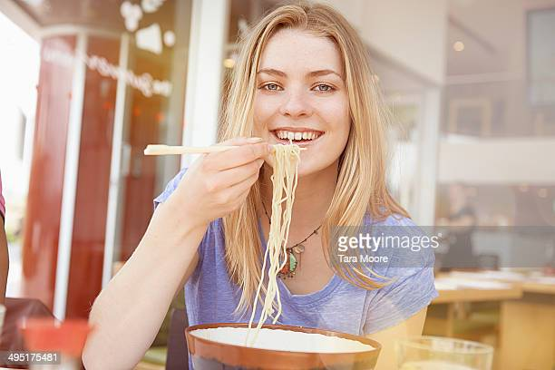 young woman eating noodles in restaurant