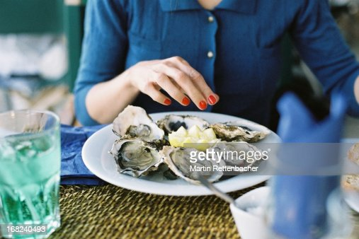 Young woman eating oysters