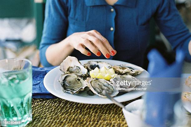 young woman eating oysters - oyster shell stock photos and pictures