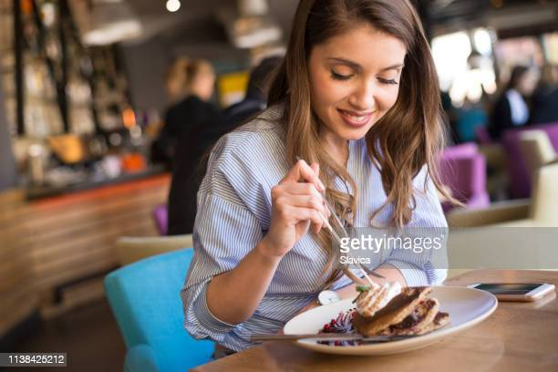 young woman eating pancakes in the restaurant - hungry stock pictures, royalty-free photos & images