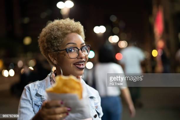 jovem mulher comendo pastel na rua depois do trabalho - colorido pastel - fotografias e filmes do acervo