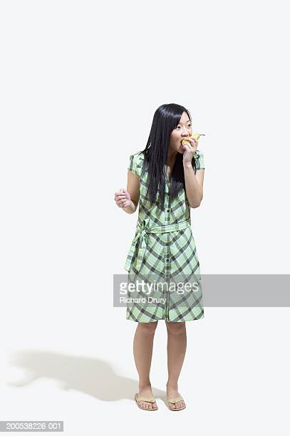 Young woman eating pear, white background