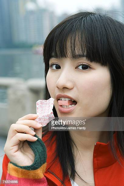 Young woman eating piece of candy, looking at camera