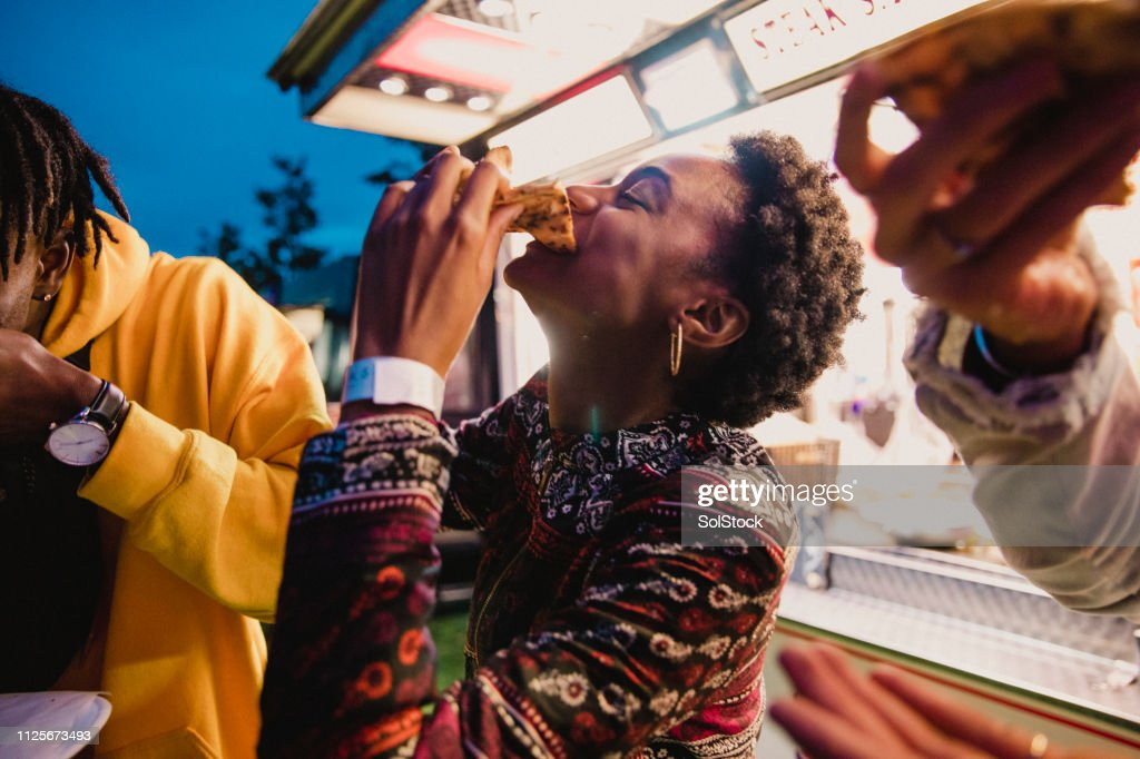 Young Woman Eating Pizza at Festival : Stock Photo