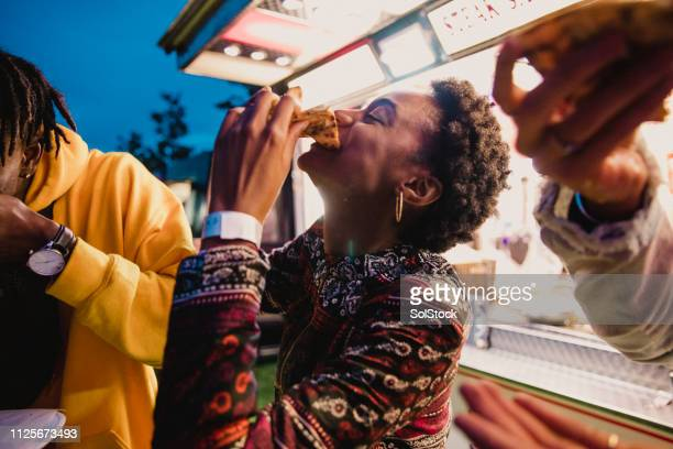 young woman eating pizza at festival - enjoyment stock pictures, royalty-free photos & images