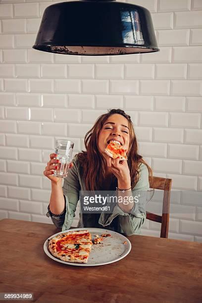 young woman eating pizza in restaurant - üppig allgemein beschreibender begriff stock-fotos und bilder