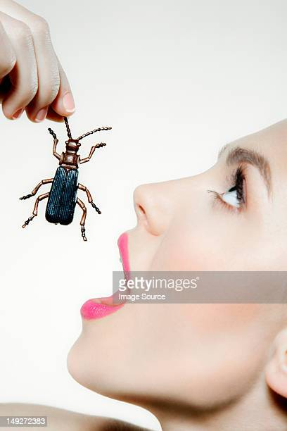 Young woman eating plastic beetle
