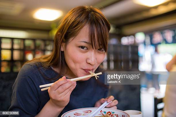 Young woman eating ramen noodle in old Japanese restaurant