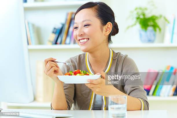 young woman eating salad and looking computer