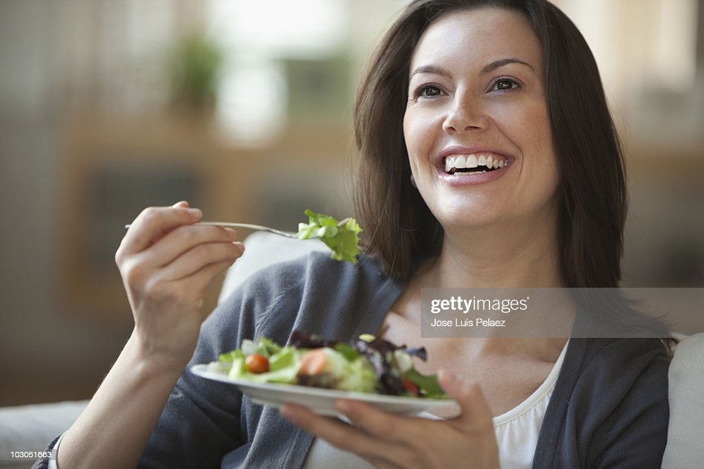 Young woman eating salad smiling : Stock Photo
