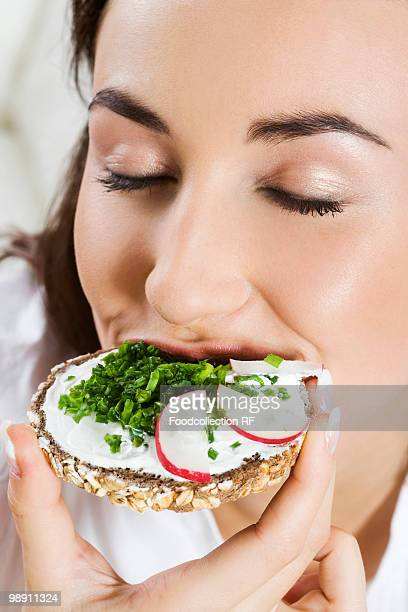 Young woman eating sandwich with wholemeal bread.