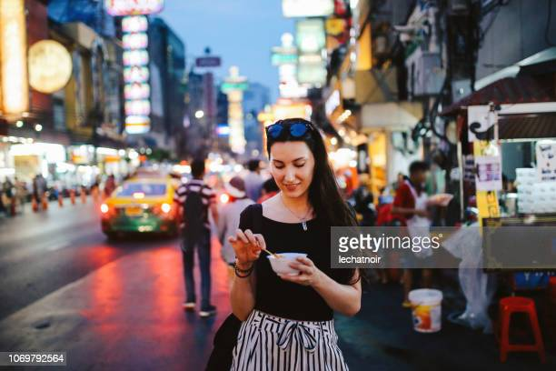 young woman eating shrimp tempura in bangkok chinatown district, thailand - street food stock pictures, royalty-free photos & images
