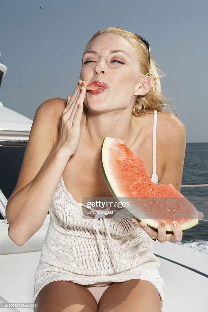 Young woman eating slice of watermelon on boat, licking finger : Stock Photo