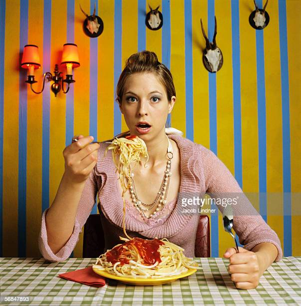 Young woman eating spaghetti, mouth open
