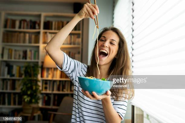 young woman eating spaghetti while sitting by window at home - speisen stock-fotos und bilder