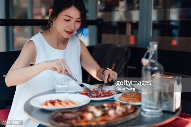 young woman eating spinach food at outdoor restaurant - real life stock pictures, royalty-free photos & images
