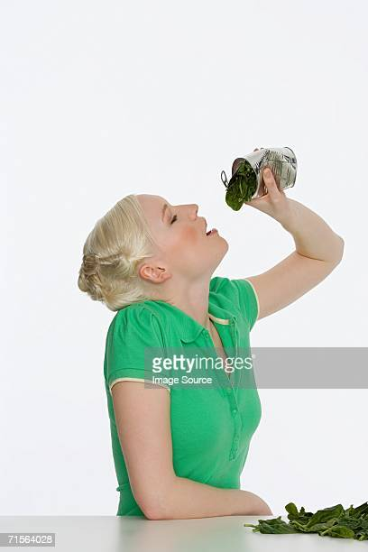 Young woman eating spinach