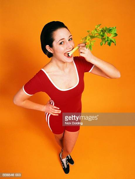 Young woman eating stick of celery, portrait, elevated view