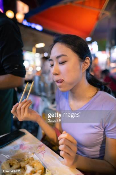 junge frau isst stinkigen tofu mit zufriedenheit auf der straße nachtmarkt - one night stand stock-fotos und bilder