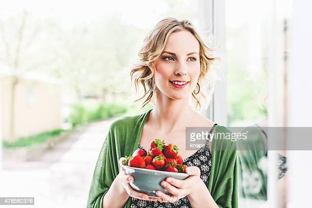 若い女性のイチゴを食べる