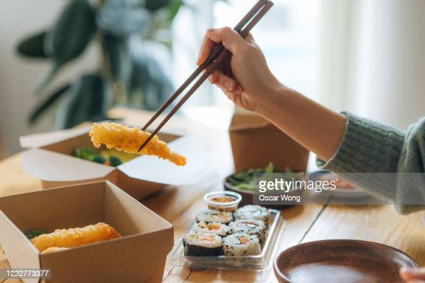 young woman eating takeaway asian meal at home - take away food stock pictures, royalty-free photos & images