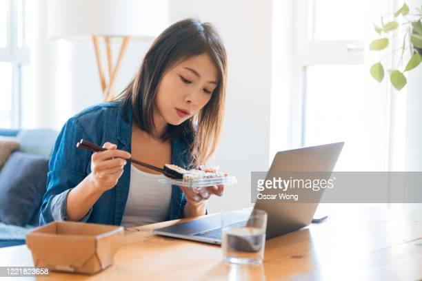 young woman eating takeaway food while working with laptop - ready to eat stock pictures, royalty-free photos & images