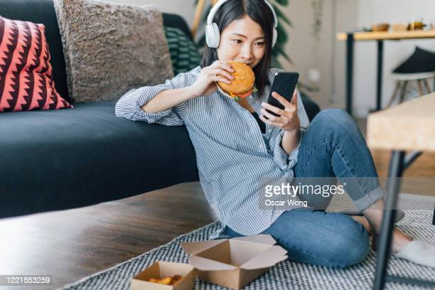 young woman eating takeaway meal while using smartphone - burger stock pictures, royalty-free photos & images