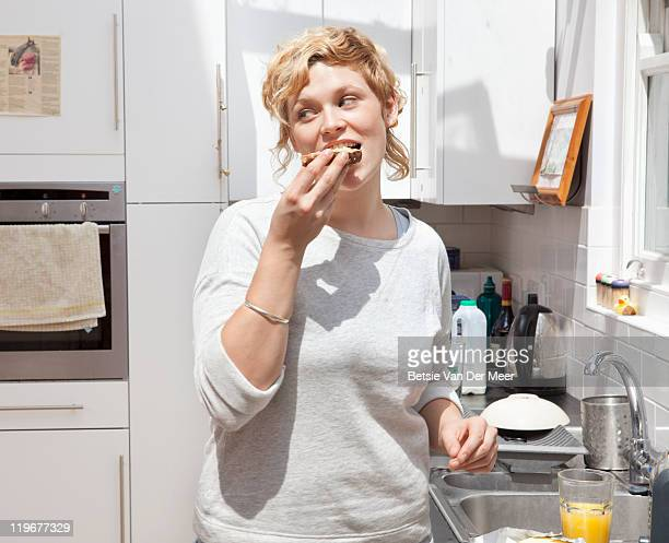Young woman eating toast in kitchen.