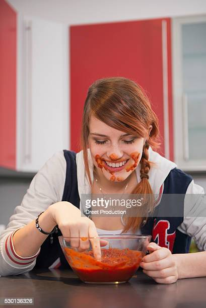 Young woman eating tomato sauce in kitchen, Munich, Bavaria, Germany